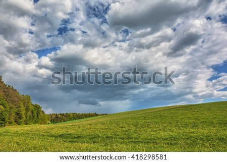 Landscape - meadows with thunderclouds over them. - stock photo