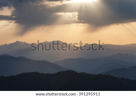 Landscape. Mountain ridges at sunset against the sky with clouds - stock photo