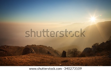 Landscape. Mountain slopes in the mist at sunset - stock photo