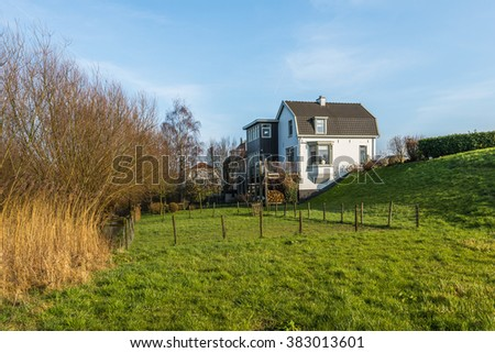 Landscape next to a Dutch dike on a sunny day in the winter season. In the foreground yellow reeds and some houses in the background. - stock photo