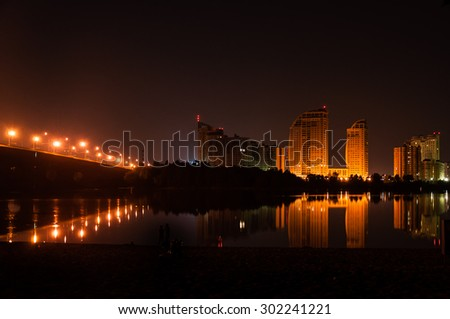 landscape night city on the river. Bridge over river - stock photo