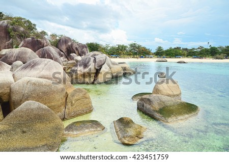 Landscape of a beach with giant-scaled granite stone boulders scattered around