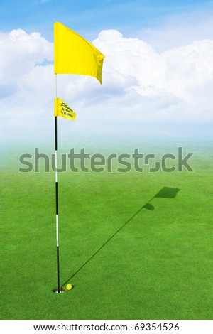 landscape of a green golf field with clouds and haze - stock photo