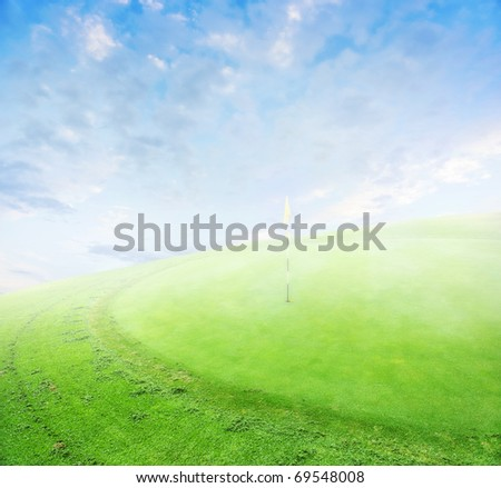 landscape of a green golf field with clouds and morning fog. Shellow focus. - stock photo