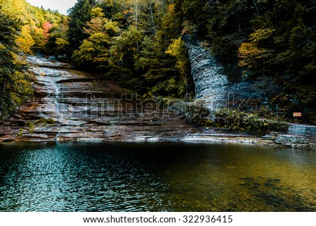 Landscape of a small waterfall down a glazed wet rock cliff next to a stone path over a small shallow lake of clear water surrounded by autumn colors - stock photo