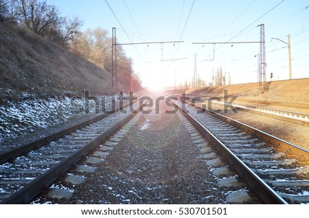 Landscape of a snowy Russian winter railway under bright sunlight. The rails and sleepers under the December snow. Russian Railways in detail