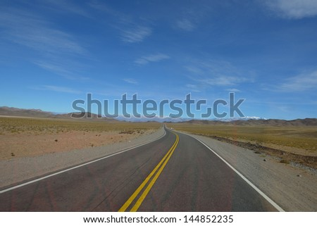Landscape of Argentina with road in the middle - stock photo