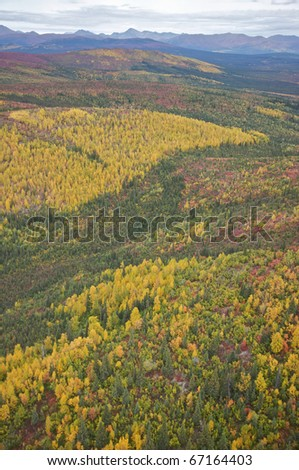 Landscape of Autumn colored hills leading up to mountains in the distance. - stock photo