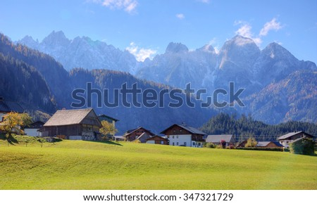 Landscape of autumn countryside with wooden farmhouses on green hill and rugged alpine mountains in the background ~ Idyllic view of Gosau village at the foothill of rocky mountains on a sunny day - stock photo