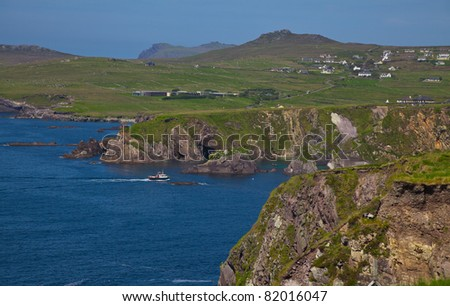 Landscape of coast of Dingle and ferry enterring Dunquin harbour and bay, Dingle Peninsula, Ireland. - stock photo