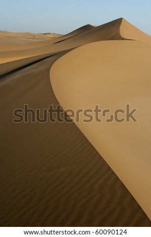 Landscape of desert sand dunes that streches into the horizon. - stock photo