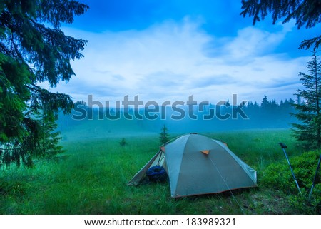landscape of fog in the field at sunrise in the forest summer, lonely tent - stock photo