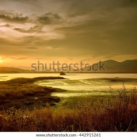 Landscape of foggy sunrise on river shot in natural colors, with grass on foreground and mountains on the horizon.  - stock photo