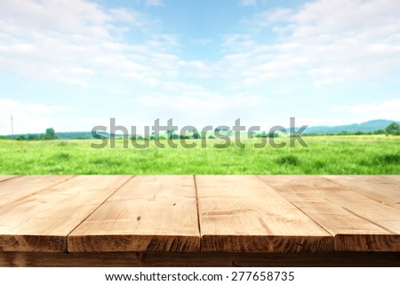 landscape of grass and sky of blue color with wooden desk top  - stock photo