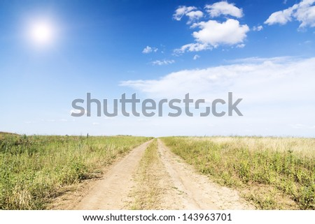 Landscape of green grass, road with track  and clouds