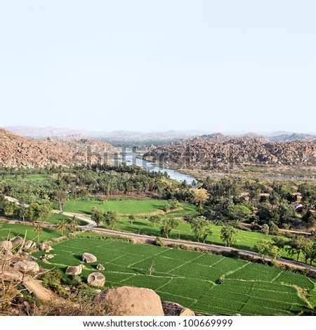 Landscape of Hampi rocks and rice fields - stock photo