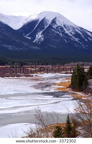 Landscape of high snowy mountains in Canadian Rockies with frozen lake