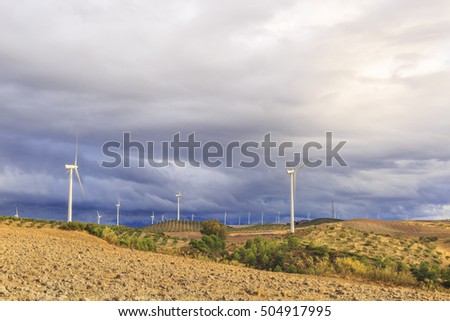 Landscape of hilly land on a cloudy day, with windfarms, olive groves and farmlands, pinewoods and other trees and shrubs