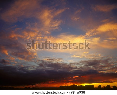 Landscape of houses silhouetted against a sunset. - stock photo