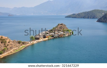 Landscape of Lugu lake with the mountain background in Yunnan, China. The lake is surrounded by mountains and has 5 islands, 4 peninsulas. - stock photo