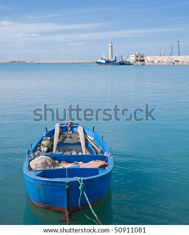 Landscape of Molfetta Seaport with close up of rowboat. Apulia. - stock photo