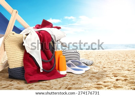landscape of ocean and beach with red towel and bag and shoes
