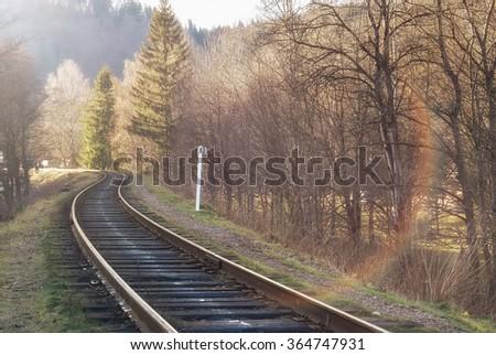 Landscape of railroad tracks across rural countryside along outskirts of a village. Sunny day. Solar flare