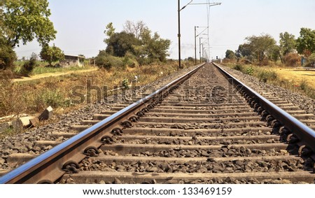 Landscape of railroad tracks in India cutting across rural countryside along outskirts of a Gujarat village near the city of Surat. Typical scene with litter thrown around and locals walking close by