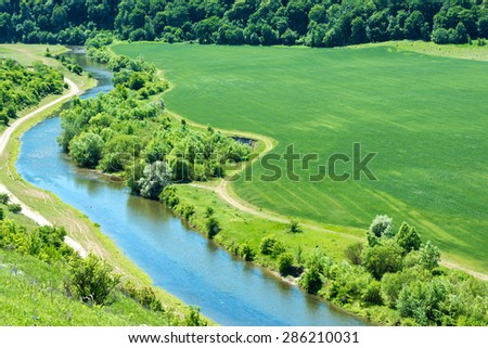 Landscape of river, green wheat field with nearby forest and country road passing by - stock photo