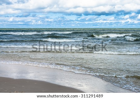 Landscape of rough sea with waves and cloudy sky. Baltic sea coast near Leba in Poland. - stock photo