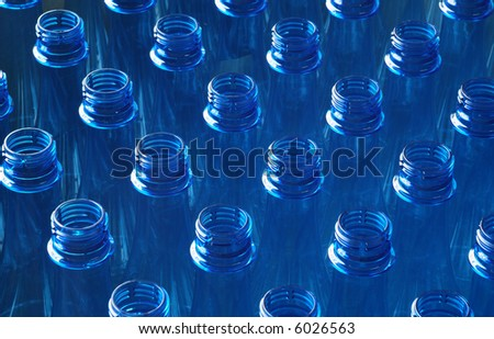 Landscape of row of many plastic blue water bottles in factory - stock photo