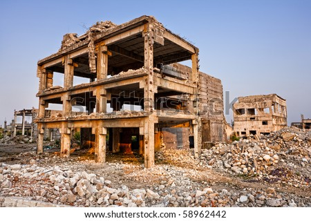 Landscape of ruined buildings at sunset, image of decrepitude or natural disaster