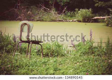 Landscape of single chair beside lake garden Vintage Styled. - stock photo