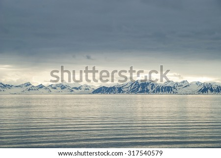 Landscape of snowy mountains by the arctic ocean, Svalbard