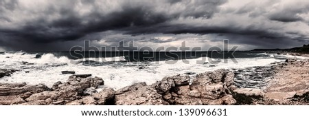 Landscape of storm on the sea, dark cloudy sky, rocky seashore, hurricane in the ocean, rainstorm, wind power, bad weather concept - stock photo