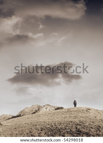 Landscape of sunset, one man go back to mountain with beautiful clouds and lights. - stock photo