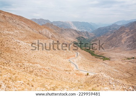 Landscape of the amazing colorful red mountains over the thin curved asphalt road in rocky canyon at cloudy weather - stock photo