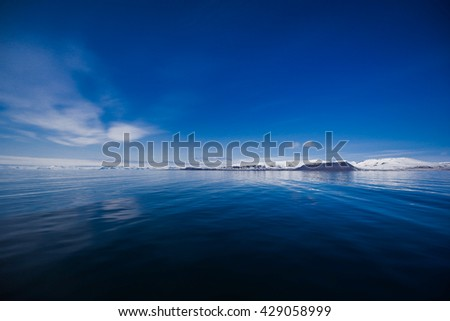 landscape of the Arctic Ocean and reflection with blue sky and mountains with snow on a sunny day, Norway, Spitsbergen, Longyearbyen, Svalbard, summer, winter