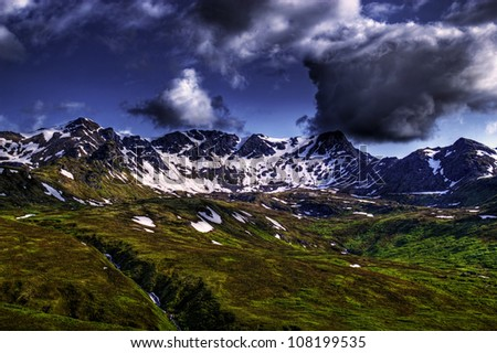 Landscape of the Talkeetna Mountains from Hatcher Pass in Alaska on a summer day with interesting clouds. - stock photo