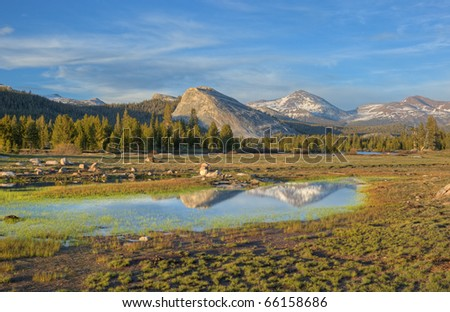 Landscape of Tuolumne Meadows and Sierra Nevada Mountains with reflections in calm water, Yosemite National Park, California, USA - stock photo