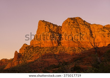 Landscape of warm light at sunset hitting a red rock cliff of Sedona, Arizona. - stock photo