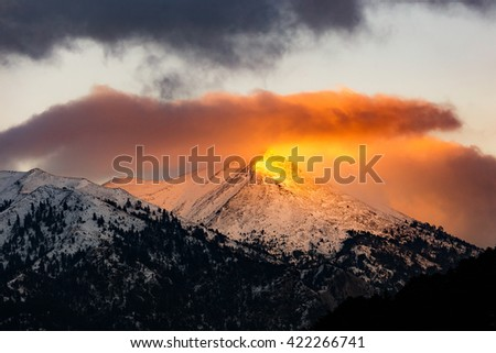 Landscape of winter mountain at dawn or sunset with golden light rays of the sun on peak in Greece - stock photo