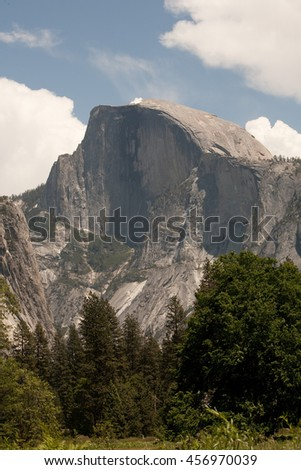 Landscape of Yosemite's famous Half Dome with a cloudy sky.