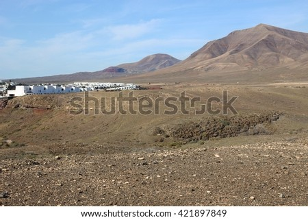 Landscape on South Lanzarote: The volcano Pico Redondo and part of Playa Blanca village and Resort. Canary Islands, Spain. - stock photo