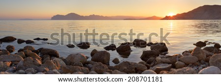 Landscape panorama at sunset. Sea shore with stones. A warm summer evening - stock photo