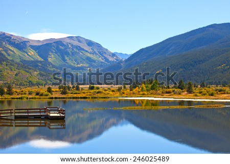 Landscape panorama of beautiful mountain nature and lake with reflections in Colorado USA on a sunny day with blue sky - stock photo