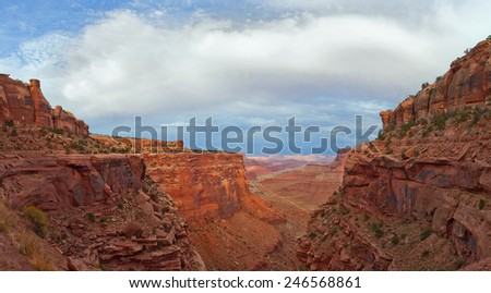 Landscape panorama of the canyon in Canyonlands national park, Utah Southwest USA. beautiful nature with red rocks and blue sky with clouds in late afternoon. View from a high point. - stock photo