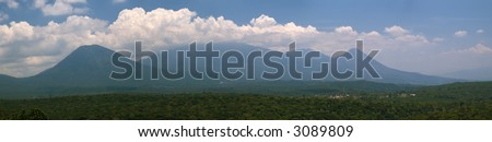 Landscape panorama showing three El Salvador volcanoes and the village of Juayua. - stock photo