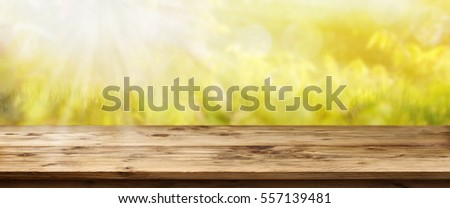 landscape panorama with sun in spring in front of a rustic wooden table