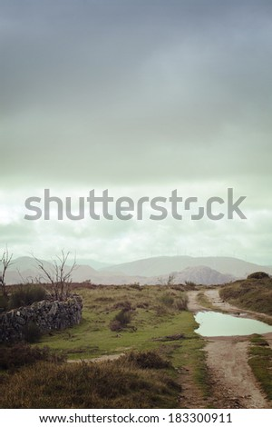 Landscape: path after the rain with some water and mountains in the horizon. Tras os Montes region in North of Portugal. Image for background - stock photo